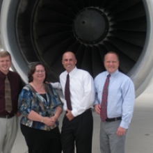Four people standing in front of a plane